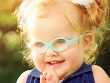 female child with glasses smiling